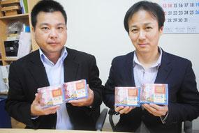 ANAで機内販売される「石垣の塩ちんすこう」を手にする宮城代表取締役(右)と喜舎場統括部長=28日午前、宮城菓子店