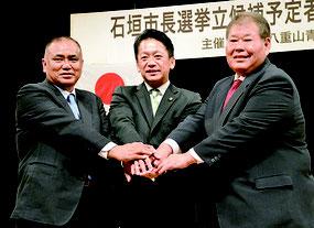 石垣市長選の公開討論会で握手する砂川氏、中山氏、宮良氏(左から)=2日夜、石垣市民会館大ホール
