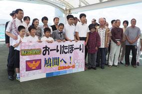 約人の島民が福井大臣を出迎えた=22日午後、鳩間港