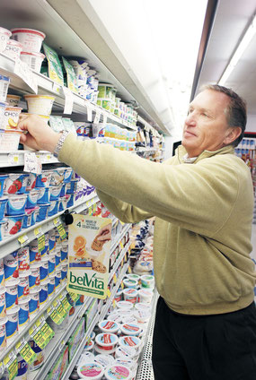 RandY Bender, owner of Bender's Foods in Bellevue, faces stock in the dairy section of the store, which first opened in 1991.