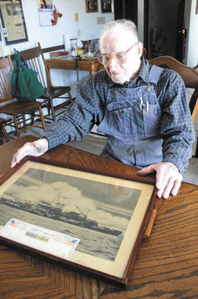 Vernon Weber of St. Donatus displays a photo of his seapleane tender, the USS Shelikof on which he served aboard during Pacific Theatres battles in World War II.