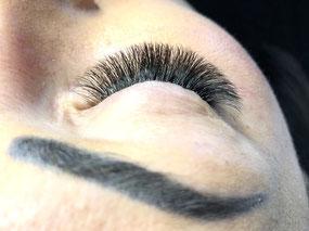 Cette photo représente un oeil de femme fermé, et met en avant une pose d'extensions de cils en volume russe.