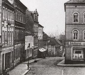 """Die """"Pirnaische Gasse"""", heute Pirnaer Straße, vom Markt aus gesehen. Das erste Knoblochsche Haus Nr. 3 ist auf der linken Seite das Haus mit den Markisen. Auf der Abb. ist es bereits als späteres """"Kaufhaus Grotfeld"""" aufgestockt."""