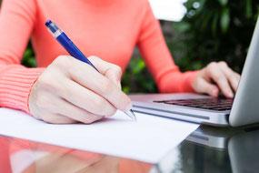 Frau in rotem Pullover schreibt am Tisch