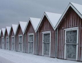 Foto einer Reihe verschneiter, roter Holzhütten