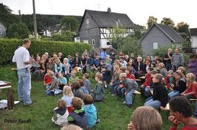 Fledermausveranstaltung auf Wiese mit Referent und Kindern