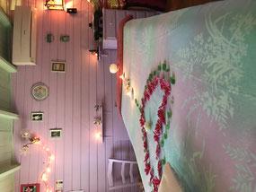 Vue de la table de massage recouverte d'un drap blanc avec un cœur dessiné en fleurs de capucines