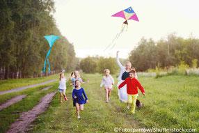 Kinder rennen und lassen Drachen steigen