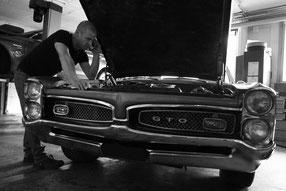 Garagist vor geöffneter Motorhaube Pontiac GTO