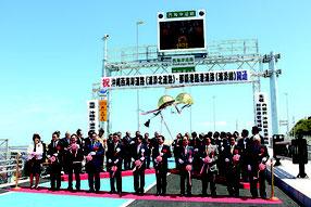 開通を記念した関係者によるテープカットとクス球開披。この後、地域の子供らによる空手演舞やエイサーが披露された=18日、浦添市港川