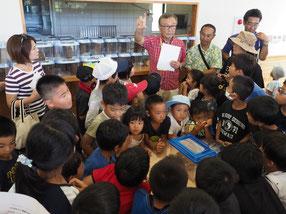 昆虫館の山田館長から育て方の説明を聞く子どもたち=23日午後、バンナ公園