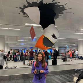 Mia figlia al nastro bagagli sotto un puffin gigante