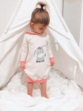 Mädchen trägt eine Tunika. Auf der Vorderseite befindet sich ein Esel. Die Tunika geht bis zu den Knien und ist rosa-weiß.