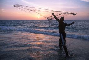 Un pescador lanza su red al atardecer en la costa de Gabón © Martin Harvey / WWF