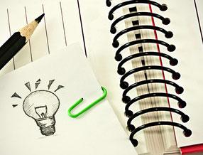 notizblock mit stift und gezeichneter glühbirne