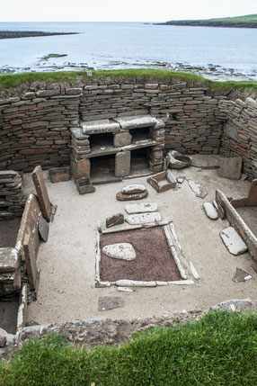 """Abbildung: Typischer Aufbau eines neolithischen Hauses in Skara Brae; Feuerstelle in der Mitte, Betten links und rechts davon, gegenüber des Eingangs die """"Kommode"""" / © Klaus Schindl"""