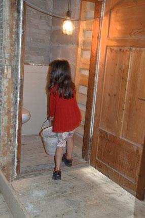 Die erste Benutzerin der Toilette mit notwendigem Wassereimer