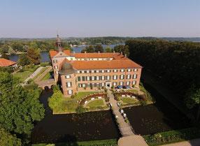 Blick von schräg oben auf das vierflüglige Schloss Eutin mit Park und Brücke über einen Wassergraben