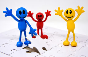 Bild von weißem Puzzle, auf dem eine blaue, eine rote und eine gelbe Figur stehen