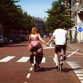 Couple cycling holding hands on a bike tour
