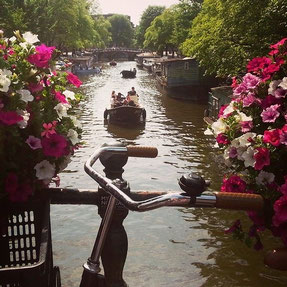 A canal view with a bike leaning on a bridge in Amsterdam