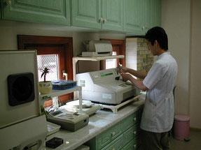 検査室でスタッフが血液検査をしている画像です