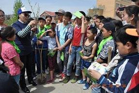コーディネーターに苗木の植え方を教わる子どもたち
