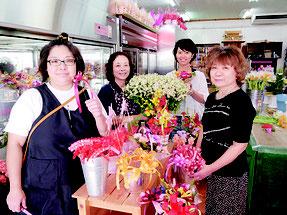 左からスタッフの下地尚さん、オーナーの石垣良子さん、娘の宮良絵梨さん、母の日の贈り物を求めて来店した顧客=花屋「ラビット」