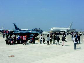 美ら島エアーフェスタ2016で展示された戦闘機の前で記念写真を撮る観客ら=10日、航空自衛隊那覇基地