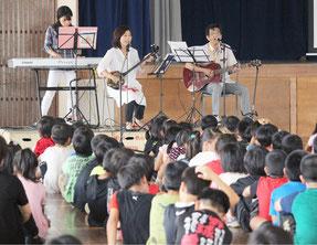 登野城小学校で平和集会が開催され、浦崎喬校長(右)は自作の曲を披露した=18日午前、同校体育館