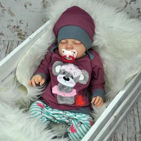 Babykleidung Baby trägt eine Beanie in beere mit grauen Punkten. dazu eine Pumphose mit Ballerinas und ein Longshirt in beere mit einer Ballerinamaus. Bestickt.