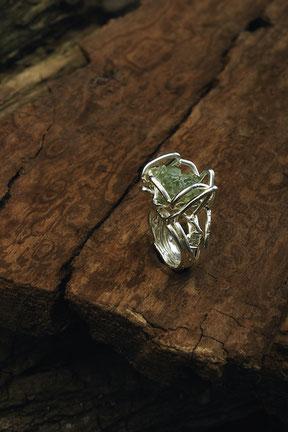 Bague en argent avec une pierre à cristaux verts qui repose sur du bois