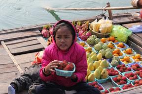 水上生活をしている親子が小型の木船でフルーツを売りに来た。