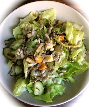 Grüner Salat mit Grillkäsewürfeln und Sonnenblumenkernen