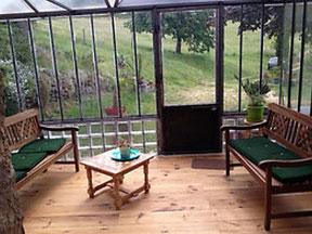 Intérieur de la véranda vitrée ouvrant sur la nature, une vallée avec des arbres, une table basse, un salon de rotin par gite de la gite de la gorre à louer en ardeche