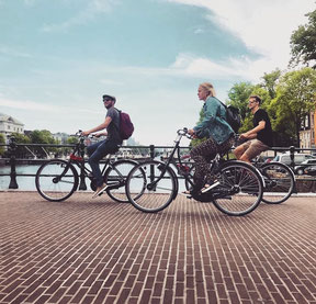 Guided tour in Amsterdam with cyclist cycling over bridge