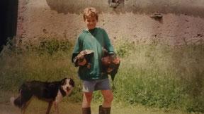 Grégoire enfant tenant deux poules dans ses bras à la ferme bio de la Millanchère