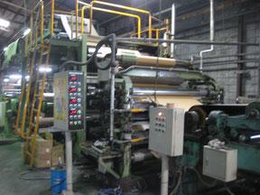 写真:コルゲータ。原紙を貼り合わせる機械です。原紙とはダンボールの原料のことで、みなさんから出されたいらなくなったダンボールがリサイクルされ、製紙メーカーから運ばれてきます。ダンボールの波(段目)をつくり糊で貼り合わせます。