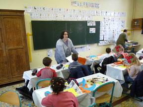 """L'illustratrice Cloé Perrotin réalisant un atelier """"Cartes aux trésors à la manière des lutins"""" dans une classe de CP à l'école de Donzy en Bourgogne-Franche-Comté"""