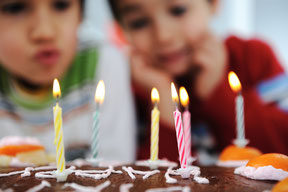 Kinder pusten Kerzen auf Geburtstagskuchen aus