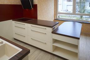 Küchenblock mit angrenzendem Tisch, Kochfeld und Glasdunstabzug