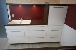 Schrankelement mit Abfallauszug links und integrierter Spülmaschine rechts oben. LED-Beleuchtung im Regalboden