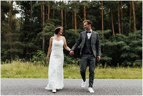 bride and groom cross the street while posing for wedding photographer
