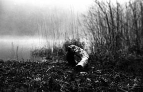 analoge zwart/wit foto van een boomstronk naast het water in het bos.