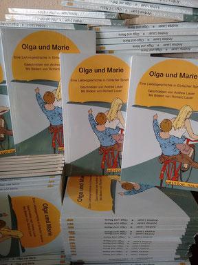 Zu sehen: Ein riesiger Stapel Bücher. Alles die Gleichen. Alles Olga und Marie. Zwei Frauen sitzen darauf auf einem Fahrrad. Fahren Richtung Sonne.