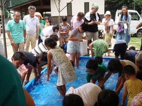 第10回新山郷村テント市。魚のつかみ取りは子ども達に大盛況でした。透明感のあるプールの水は、近くの千代川から汲み上げたものです。