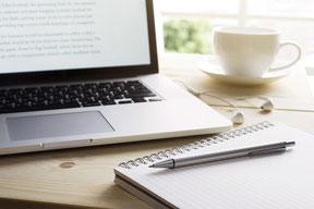 Laptop und Notizblock mit Stift