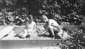 Schwarzweißfoto: zwei Kinder im Sandkasten