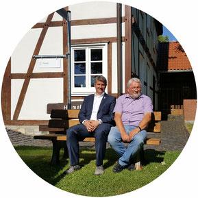 Bürgermeister Remco van der Felden und Franz Pieper testen die Mitfahrbank