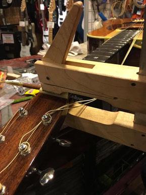ギターナットを機械で取り付けている作業